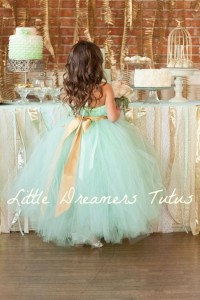 This flower girl dress in mint green with a gold sash