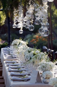 Long tables with white linens and arrangements of peonies and sweet  peas are the perfect setting for a seated dinner reception.