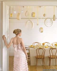 Lengths of paper and ribbon coiled into airy circles and raindrops dangle at different heights above the table